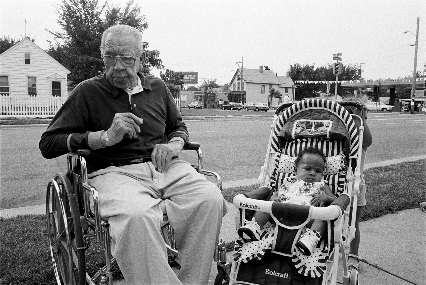 An old man in a wheelchair sits next to a baby in a stroller