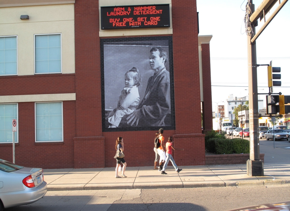 People walking down the sidewalk look at a large photo on the side of a building of a man with a child on his lap