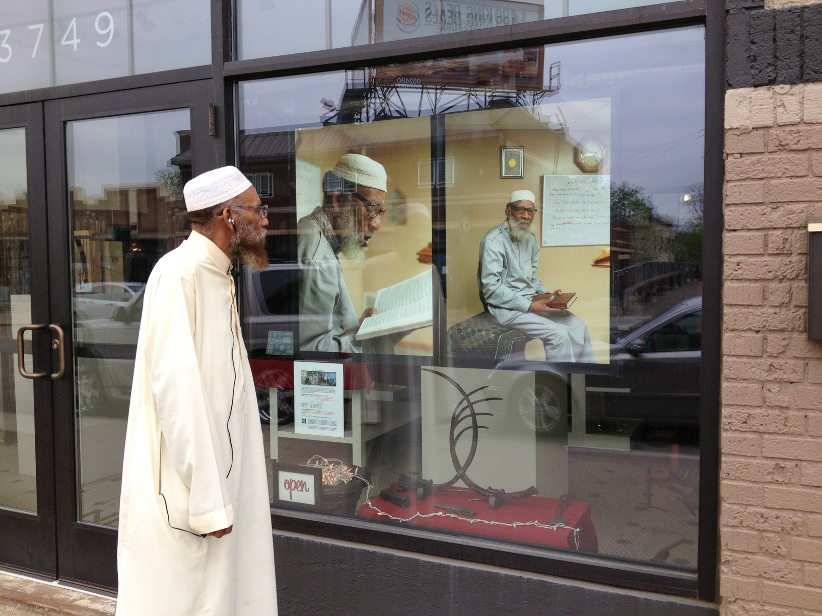 A man looks at photos of himself displayed in the window of a business for a public art display