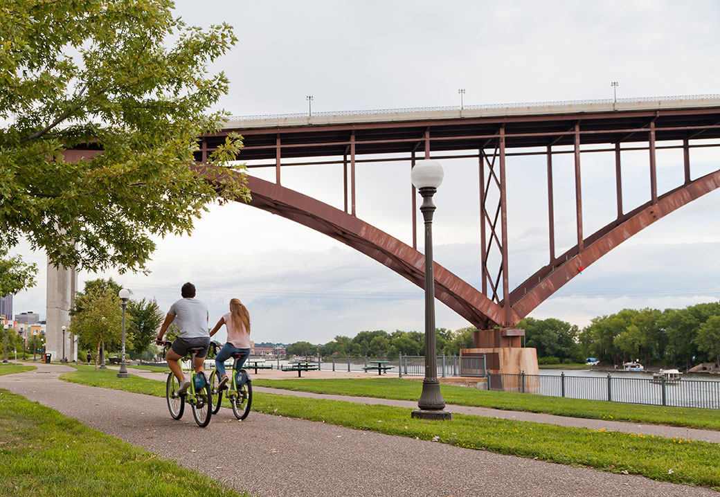 A couple riding bicycles along Mississippi River in St. Paul, MN. Photo credit: Bogdan Denysyuk/Shutterstock.com