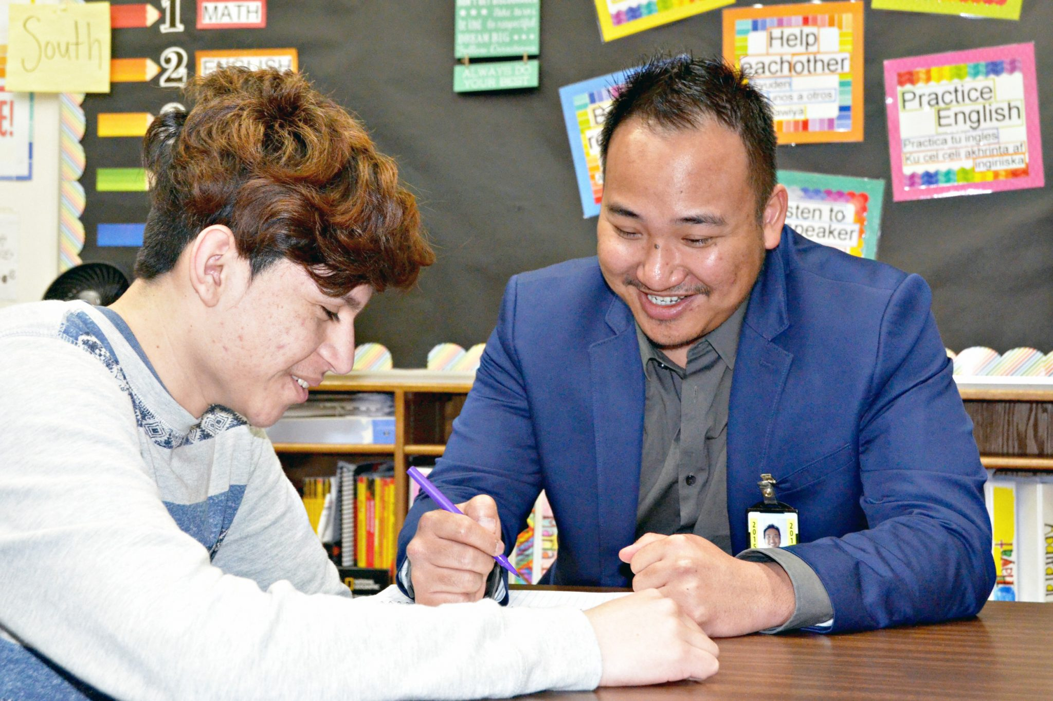Sam Ouk, an English Language Coordinator for Faribault Public Schools, works with a student.