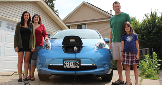 a family standing next to an electric car