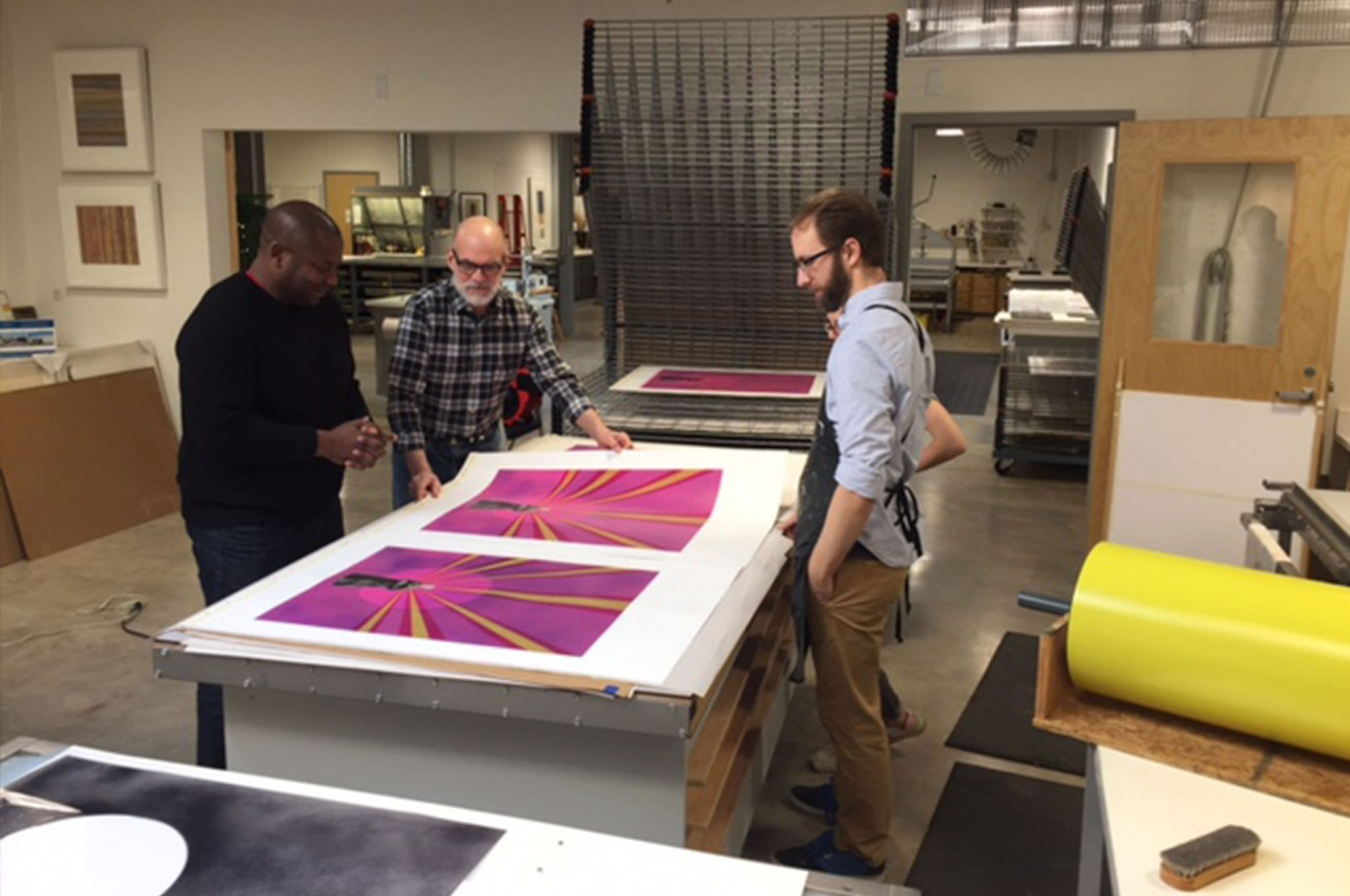 Visiting artist Rico Gatson, Cole Rogers, a master printer, and Zac Adams-Bliss, a senior printer, review printer proofs at Highpoint.