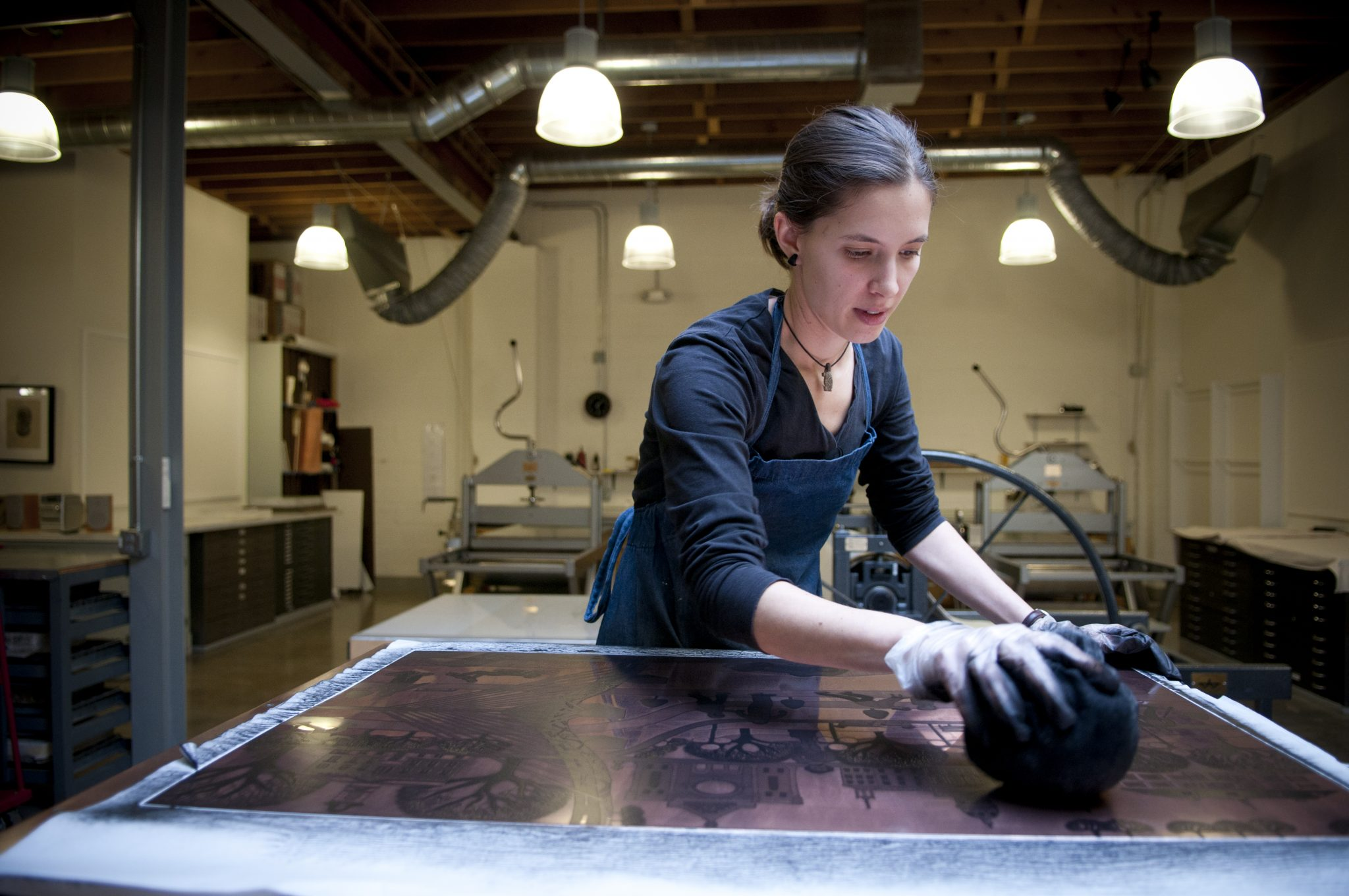 Co-op artist Miriam Rudolf wipes ink on an etching plate, preparing it so she can print on the press.