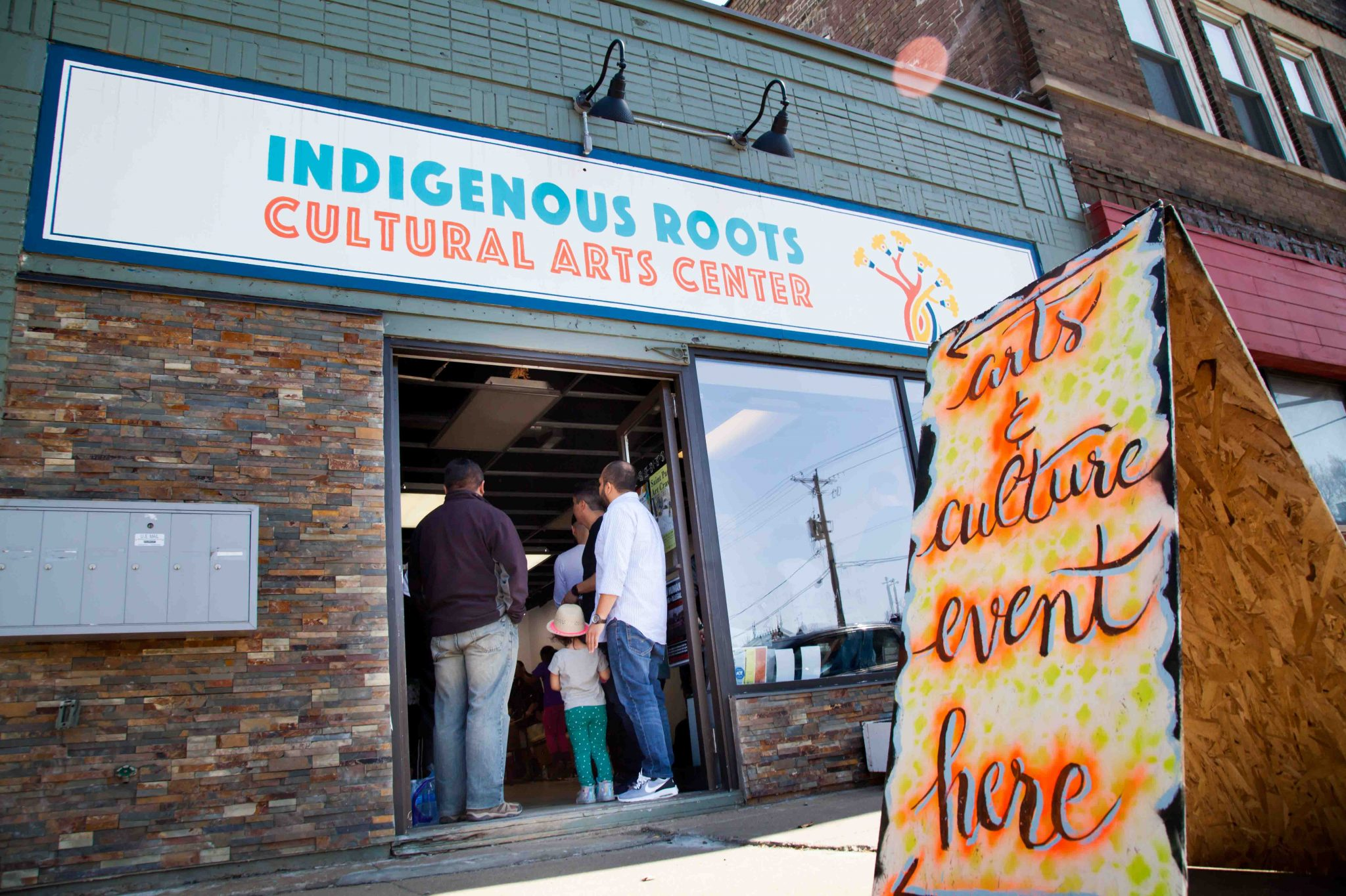 A group of people enter the Indigenous Roots Cultural Arts Center for an event