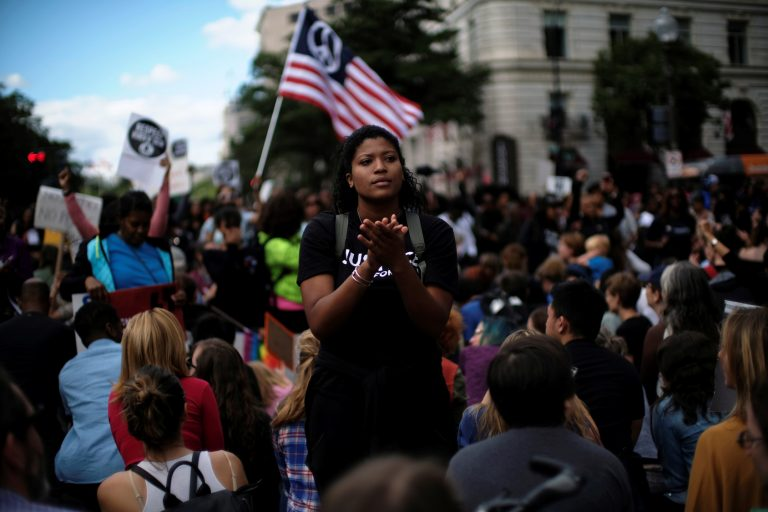 A Woman Applauds As Protesters Kneel On One Knee Outside The Trump International Hotel On Pennsylvania Avenue During The March For Racial Justice Calling For Racial Equity And Justice In Washington