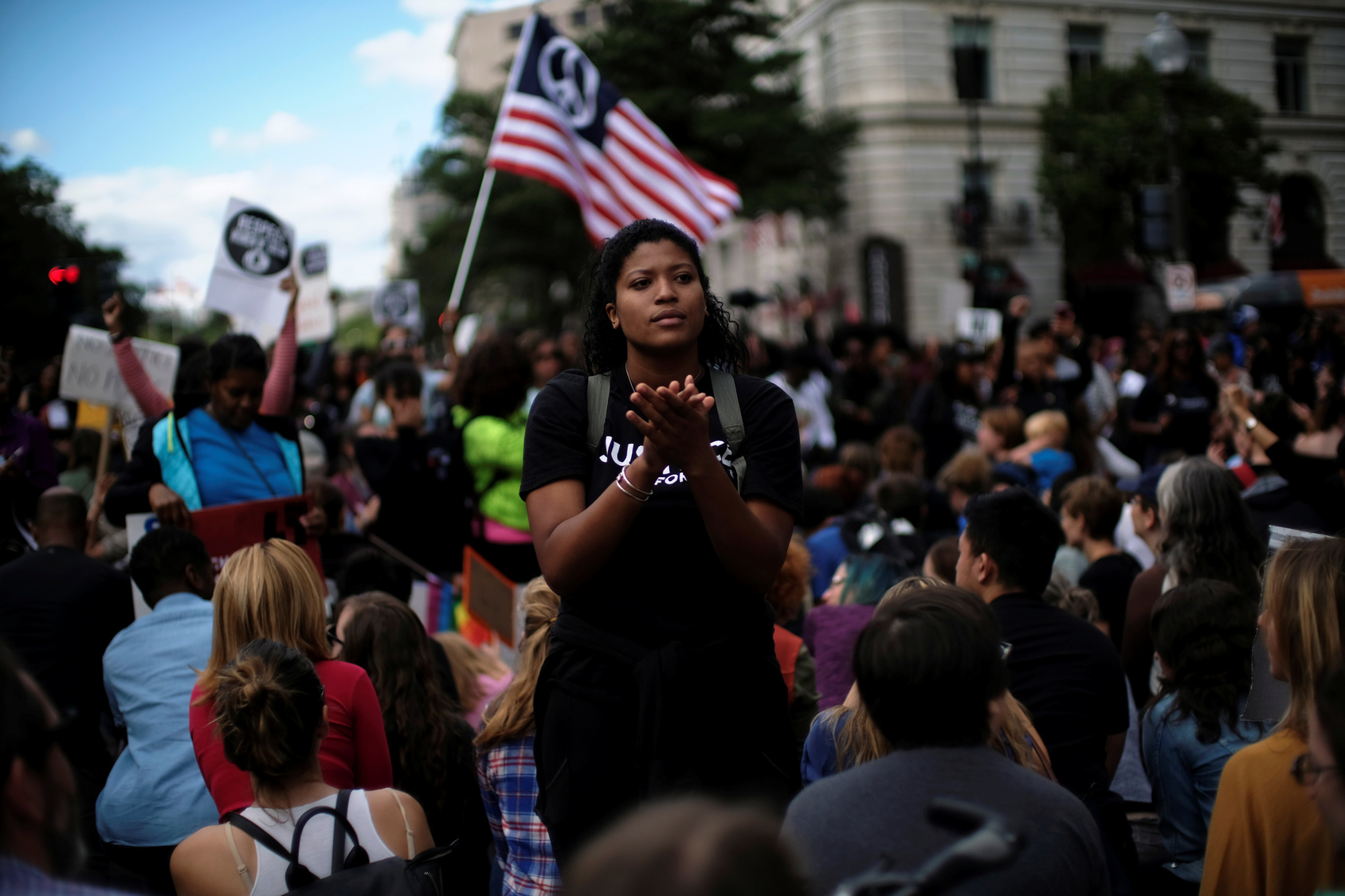 A Woman Applauds As Protesters Kneel On One Knee Outside The Trump International Hotel On Pennsylvania Avenue During The March For Racial Justice Calling For Racial Equity And Justice In Washington in September 30, 2017.