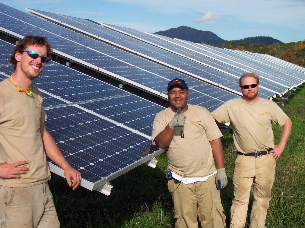 three men standing infront of solar panels