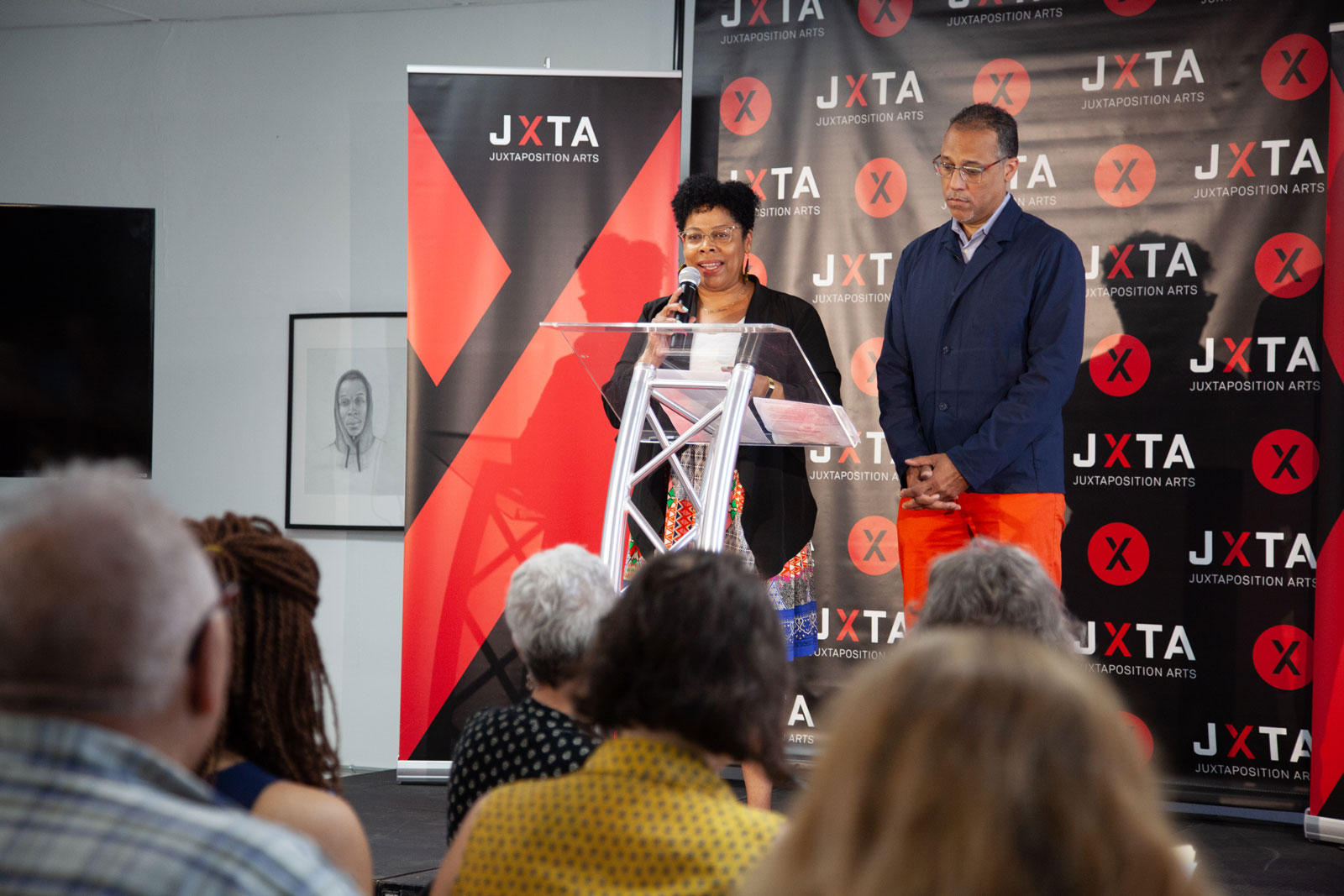 Two people stand at a podium and talk to a crowd.