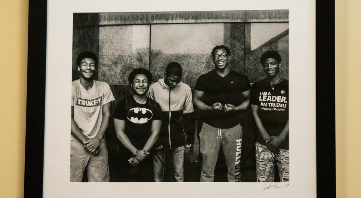 A black and white photograph that shows five young black men smiling and laughing