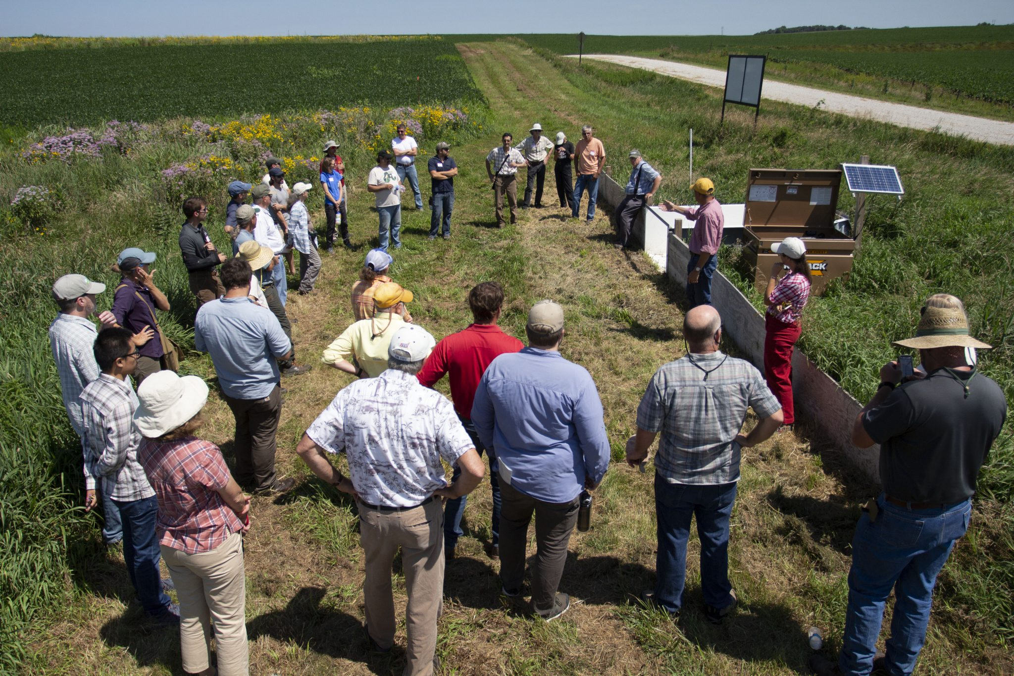 Farmers, land owners, scientists, and extension specialists gather to discuss research and implementation of prairie strips on commercial farms at Iowa State University Armstrong Memorial Research and Demonstration Farm, Lewis, Iowa. Prairie strips reduce soil and nutrient loss from corn and soybean farms while also supporting more diverse and abundant wildlife.
