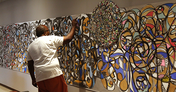 an African American man painting a wall